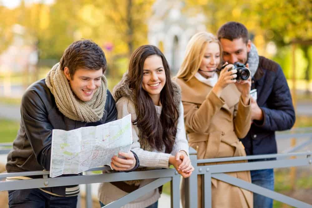Group of 4 adults, 2 taking a photo and 2 looking at a map