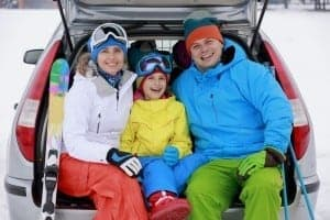 FAmily sitting in the trunk of their car with ski gear