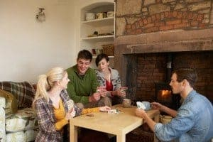 Family playing cards at a table in a cabin