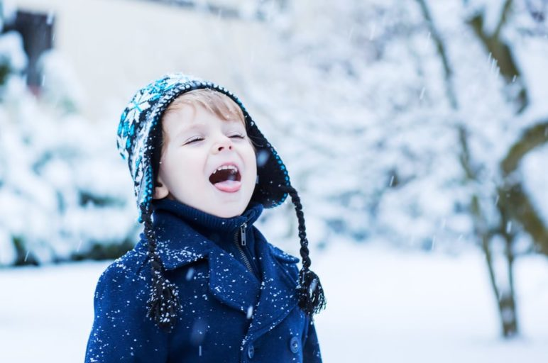 Little boy catching snowflakes on his tongue outside of a three bedroom Pigeon Forge cabin