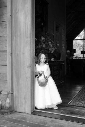 A black and white photo of a little girl at a wedding.