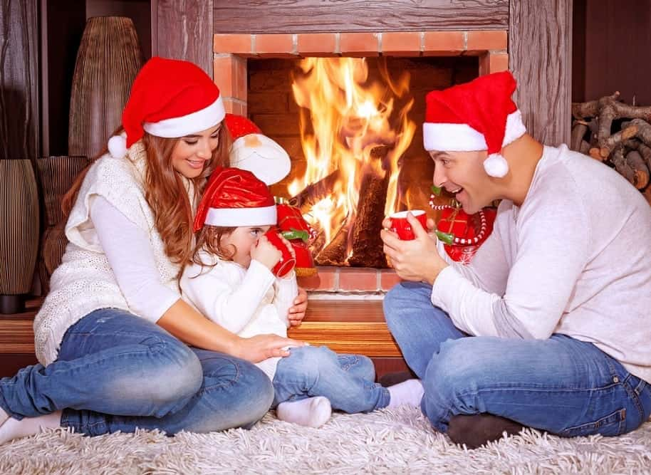 Happy family celebrating Christmas in front of the fireplace in a cabin.