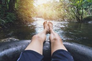 Close up of mans feet while tubing on river in Smoky Mountains