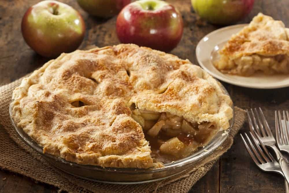 A delicious apple pie on a table with apples.