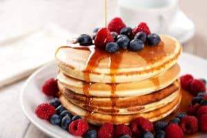 A stack of pancakes covered in berries and syrup.