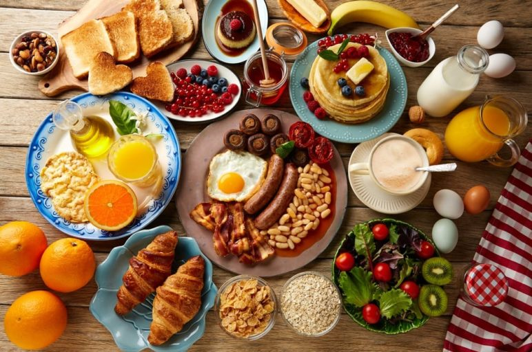 A variety of foods from a breakfast buffet on a table.