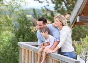 family on deck of cabin in mountains